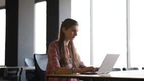 工作在膝上型计算机lndoors的一名严肃的妇女的画象 免版税图库摄影