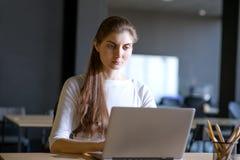 工作在膝上型计算机lndoors的一名严肃的妇女的画象 图库摄影