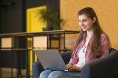 工作在膝上型计算机lndoors的一名微笑的妇女的画象 免版税库存照片