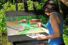工作在自然绘画的女性艺术家 图库摄影