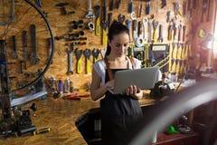 工作在自行车维修车间的少妇 免版税库存图片