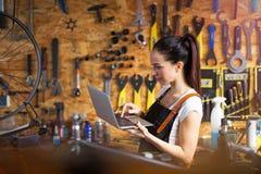 工作在自行车维修车间的少妇 免版税库存照片