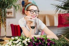 工作在花店的可爱的微笑的少妇卖花人 免版税库存照片