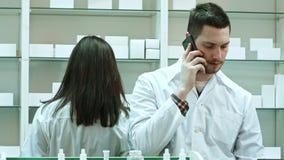 工作在药房,谈话通过巧妙的电话和检查药片的女性和男性药剂师 股票录像