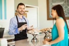 工作在蛋糕商店的年轻人 免版税库存照片