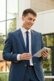 工作在触摸板的一个年轻人专业银行家的画象,当站立在内部现代的办公室空间,有目的男性en时 免版税库存照片