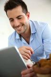 工作在触摸板的英俊的人 免版税库存照片