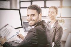 工作在计算机书桌的愉快的商人 免版税库存照片