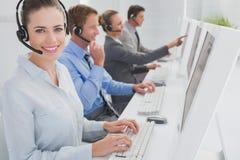 工作在计算机和佩带的耳机上的企业队 免版税库存照片