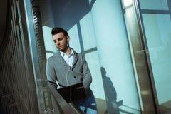 工作在计算机和听到音乐的英俊的年轻人 免版税库存图片