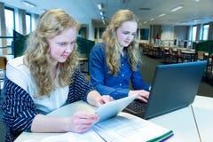 工作在计算机和片剂上的两个女孩在计算机教室 免版税库存图片