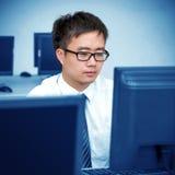 工作在计算机室的亚裔人 图库摄影