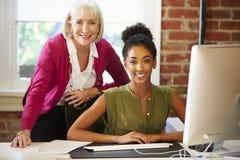 工作在计算机的两名妇女在当代办公室 免版税库存照片