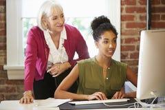 工作在计算机的两名妇女在当代办公室 免版税库存图片