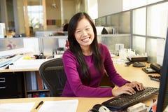 工作在计算机的亚裔妇女在现代办公室 库存照片