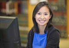工作在计算机的亚裔学生 免版税图库摄影