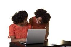 工作在计算机的兄弟姐妹或朋友 免版税库存照片