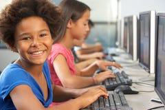 工作在计算机的基本的学生在教室 库存图片