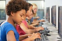 工作在计算机的基本的学生在教室 免版税库存照片