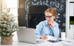 工作在计算机的女实业家自由职业者在圣诞节 库存图片
