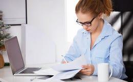 工作在计算机的女实业家自由职业者在圣诞节 免版税图库摄影