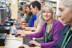 工作在计算机的小组成熟学生 免版税库存照片