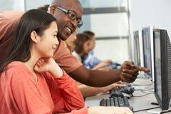 工作在计算机的老师帮助的学生在教室 图库摄影