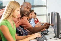 工作在计算机的老师帮助的学生在教室 免版税库存图片