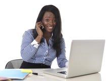 工作在计算机膝上型计算机和手机的愉快的黑人种族妇女放松了 免版税库存照片