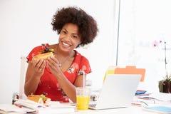 工作在设计演播室的妇女吃午餐在书桌 图库摄影