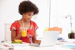 工作在设计演播室的妇女吃午餐在书桌 免版税库存照片