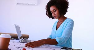 工作在设计用桌子4k的图纸的女性建筑师 影视素材