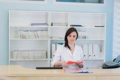 工作在诊所总台的年轻实习者医生,她回答电话和预定任命 图库摄影