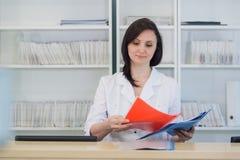 工作在诊所总台的年轻实习者医生,她回答电话和预定任命 库存图片