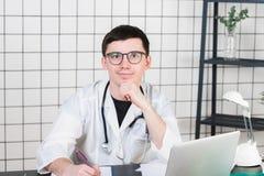 工作在诊所招待会的微笑的年轻男性医生,他使用一台计算机并且写着医疗报告 免版税库存照片