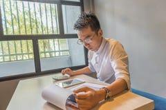 工作在财政文件和计算器的年轻亚裔会计 库存图片