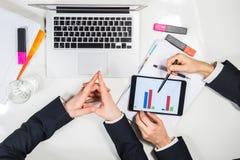 工作在财政项目或任务顶视图的现代minimalistic书桌的两个商人的概念 免版税图库摄影