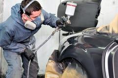 工作在车的专业汽车画家 免版税库存图片