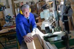 工作在车间的资深木匠 免版税图库摄影
