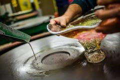 工作在转动的硅土铺沙的盘上的人一个玻璃吹的花瓶 免版税库存图片