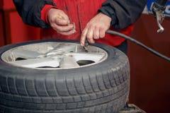 工作在轮胎的技工 库存图片