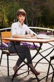 工作在边路咖啡馆的年轻时装业妇女 免版税库存照片