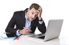 工作在重音的可爱的商人在办公桌计算机遭受的头疼 免版税库存照片