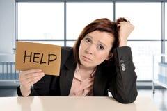 工作在重音的哀伤和沮丧的女商人在现代办公室rwindow室请求帮忙劳累了过度 免版税图库摄影