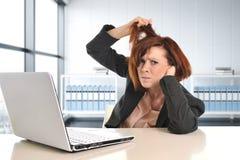 工作在重音的年轻哀伤和沮丧的女商人在拉扯她的头发的现代办公室窗口室疲倦了 免版税图库摄影