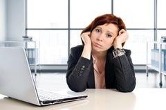 工作在重音的年轻哀伤和沮丧的女商人在现代办公室窗口室疲倦了 库存照片