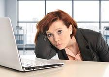工作在重音的年轻哀伤和沮丧的女商人在现代办公室窗口室疲倦了 免版税库存照片