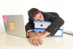 工作在重音的年轻疲乏和被浪费的商人在办公室被用尽的便携式计算机睡觉 免版税图库摄影