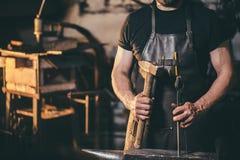 工作在铁砧的金属的铁匠在伪造 图库摄影
