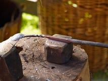工作在铁砧的金属的铁匠 免版税库存照片